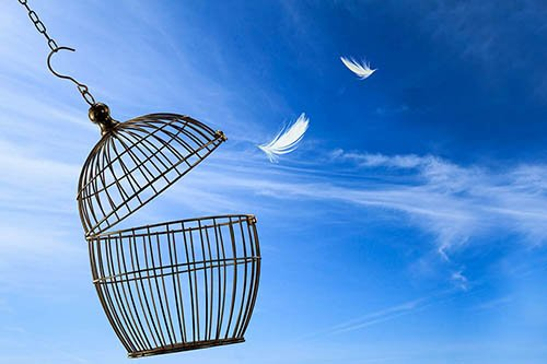 An empty bird cage over a blue cloud-filled sky